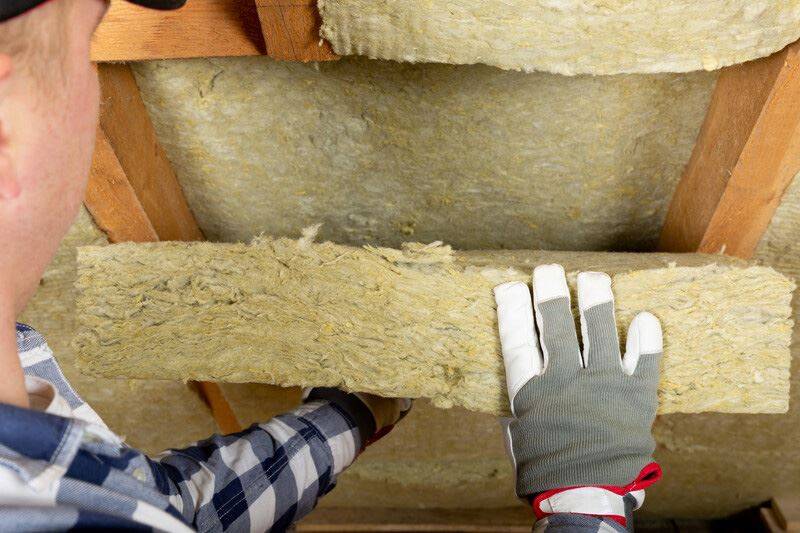pest control technician inspecting attic insultation for signs of pests